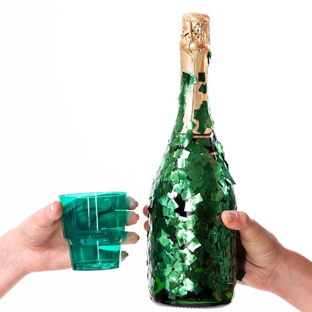 Mãos segurando um copo e uma garrafa de champanhe Foto gratuita