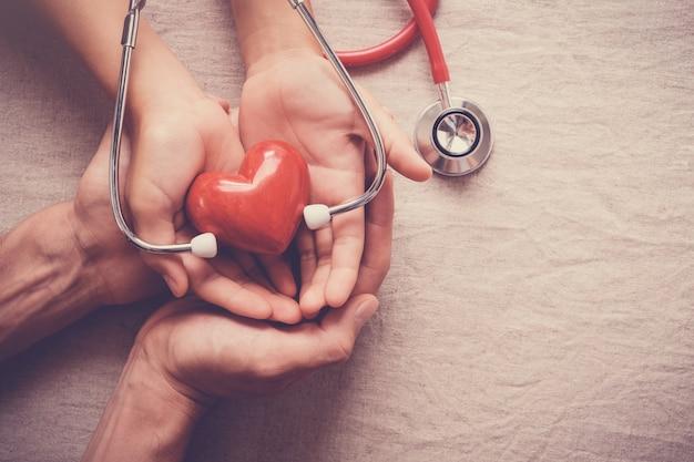 Mãos segurando um coração vermelho com estetoscópio, saúde do coração, conceito de seguro de saúde Foto Premium