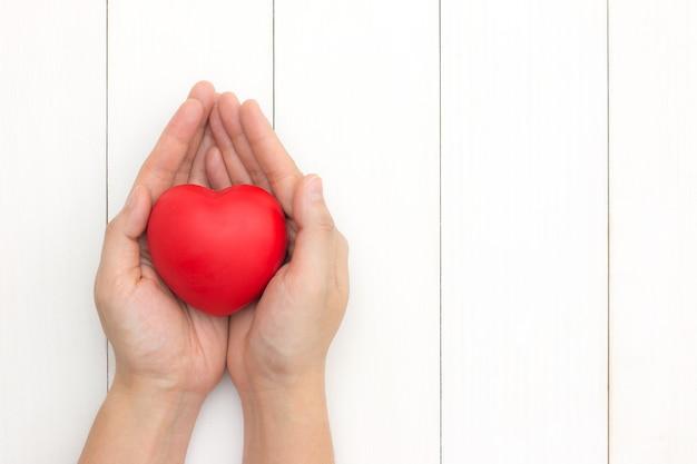 Mãos segurando um coração vermelho, cuidados de saúde, conceito de seguro. dando amor para o dia dos namorados. Foto Premium