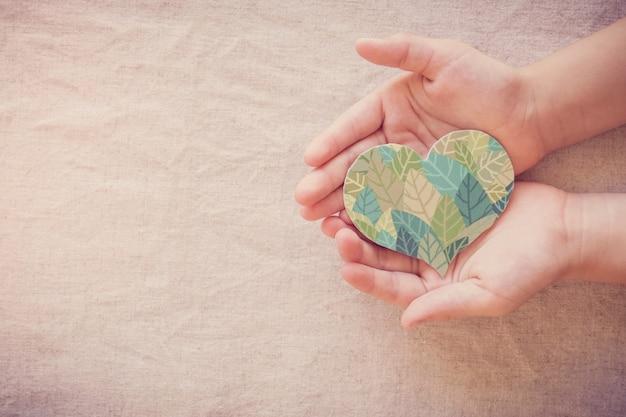 Mãos segurando um formato de coração em folha, responsabilidade social em responsabilidade social, vida ecologicamente sustentável, vegano, dia mundial do meio ambiente, dia da terra Foto Premium