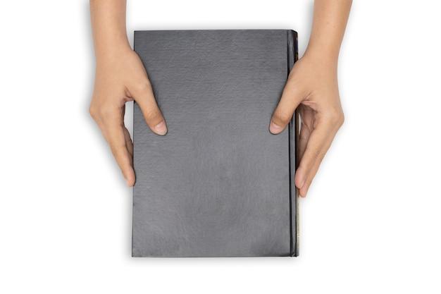 Mãos segurando um livro fechado com capa preta em branco sobre fundo branco Foto Premium