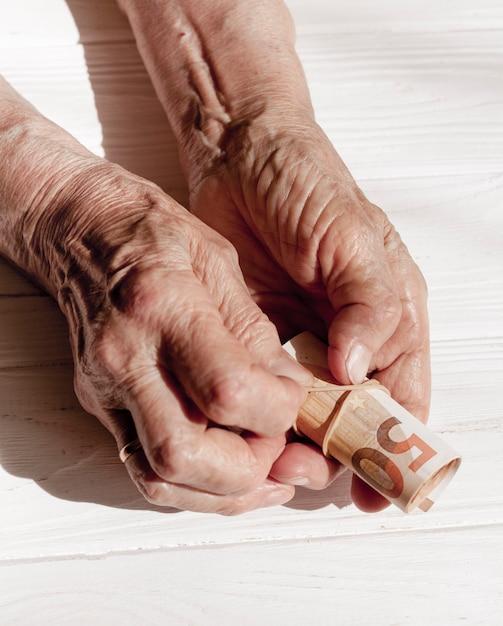 Mãos segurando um rolo de notas Foto gratuita