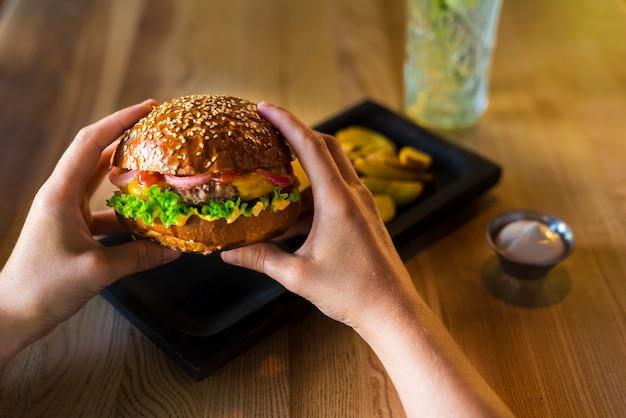 Mãos segurando um saboroso hambúrguer de carne com alface Foto gratuita
