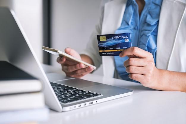 Mãos segurando um smartphone, cartão de crédito e digitando no laptop para compras on-line e compra de pagamento Foto Premium