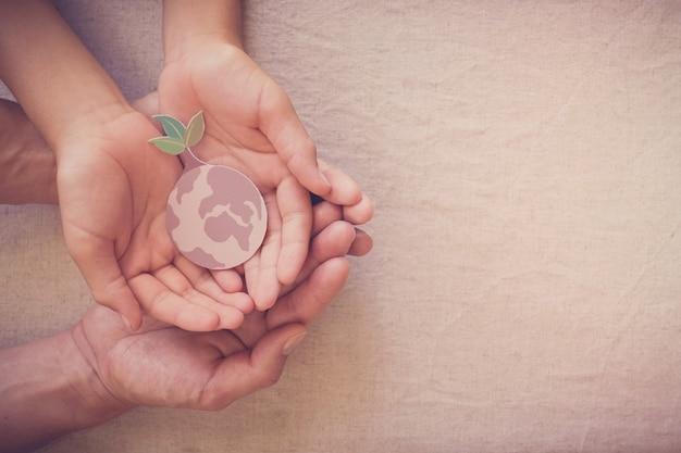 Mãos segurando uma árvore em crescimento na terra, salvar o planeta, dia da terra, ambiente de ecologia, ação climática de emergência, responsabilidade social de rse, conceito de vida sustentável Foto Premium