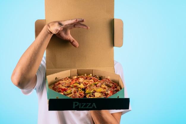 Mãos segurando uma caixa com pizza Foto Premium