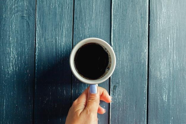Mãos segurando uma caneca de bebida quente na mesa de madeira Foto Premium
