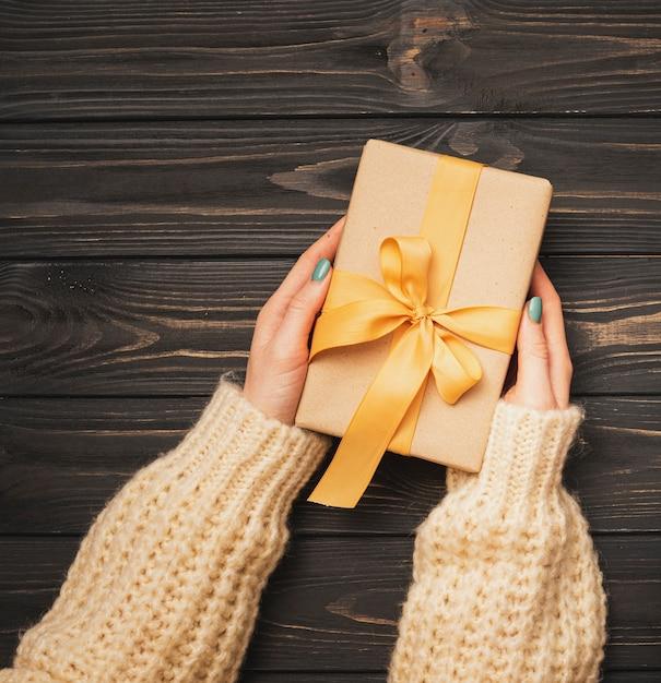 Mãos segurando uma fita dourada amarrada presente para o natal Foto gratuita