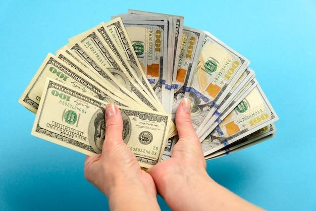 Mãos segurando uma nota de 100 dólares. mãos segurar um monte de dinheiro. ventile as contas de dólares americanos Foto Premium