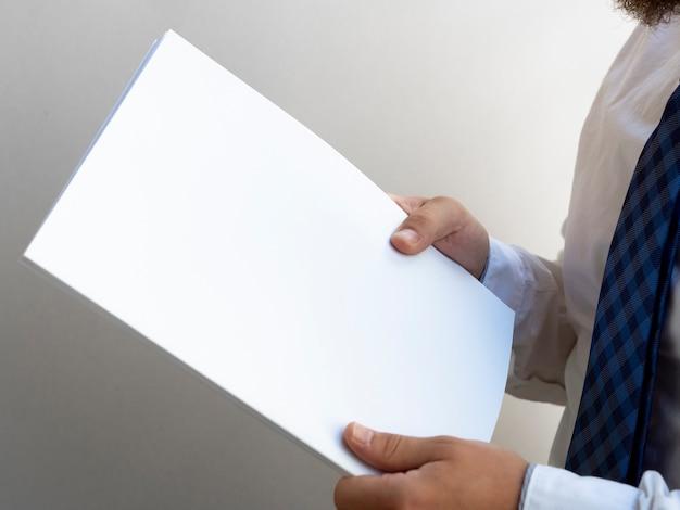 Mãos segurando uma pilha de maquete de papel Foto gratuita