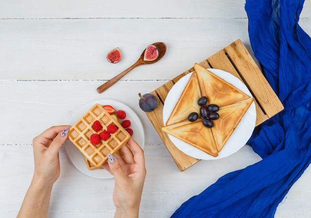 Mãos segurando waffle com bagas e frutas em um prato branco sobre uma superfície branca Foto gratuita