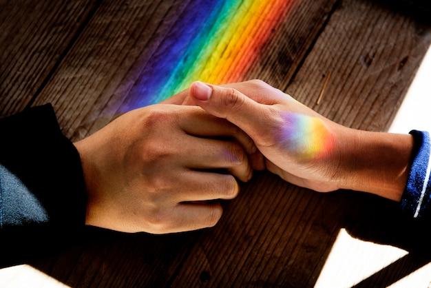 Mãos segure junto com as luzes de prisma Foto gratuita