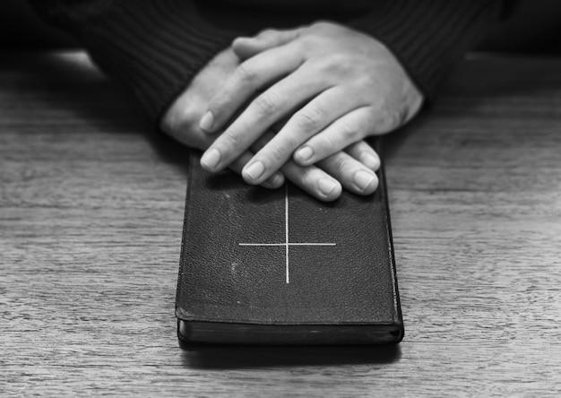 Mãos sobre a bíblia na mesa de madeira Foto gratuita