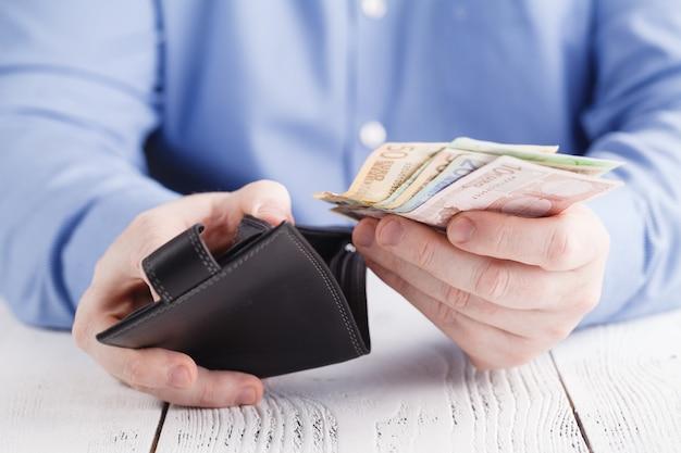 Mãos tirando dinheiro da carteira Foto Premium