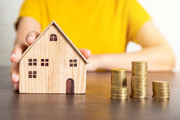 Mãos tocando moedas e casa de brinquedo Foto Premium