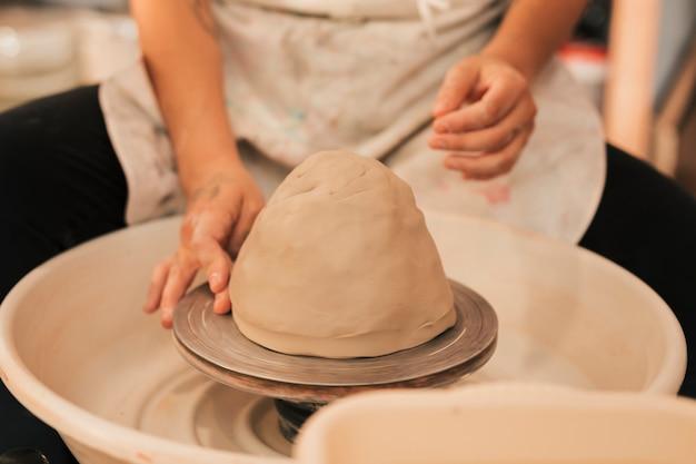 Mãos trabalhando na roda de oleiro Foto gratuita