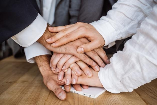 Mãos unidas da equipe de negócios sobre fundo de espaço de trabalho Foto gratuita
