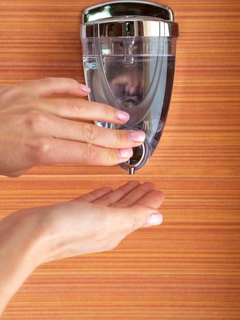 Mãos usando saboneteira Foto gratuita