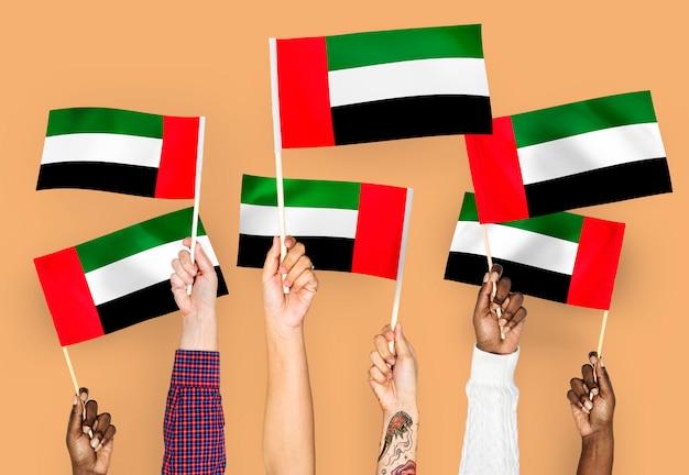 Mãos, waving, bandeiras, de, a, emirates árabes unidos Foto gratuita