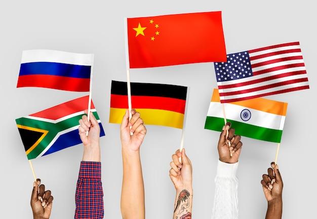 Mãos, waving, bandeiras, de, china, alemanha, índia, áfrica sul, e, rússia Foto gratuita