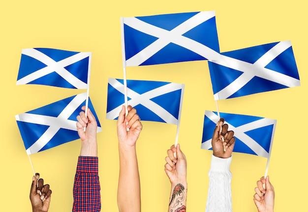 Mãos, waving, bandeiras, de, escócia Foto gratuita
