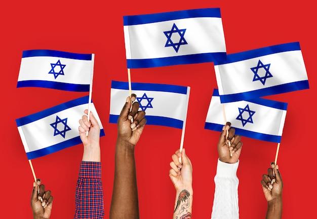 Mãos, waving, bandeiras, de, israel Foto gratuita