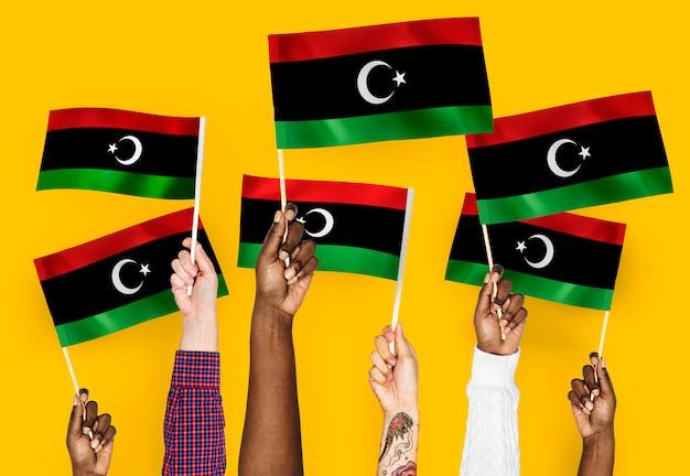 Mãos, waving, bandeiras, de, líbia Foto gratuita