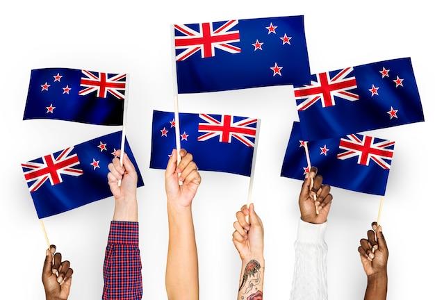 Mãos, waving, bandeiras, de, nova zelândia Foto gratuita