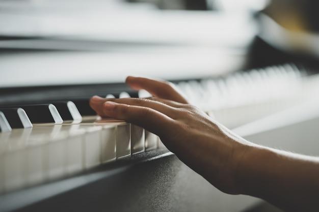Mãozinha tocando piano de música piano vertical Foto Premium