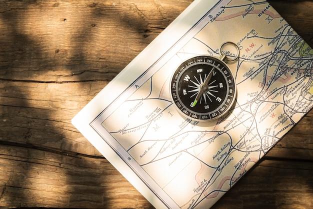 Mapa e bússola com fundo de madeira Foto gratuita