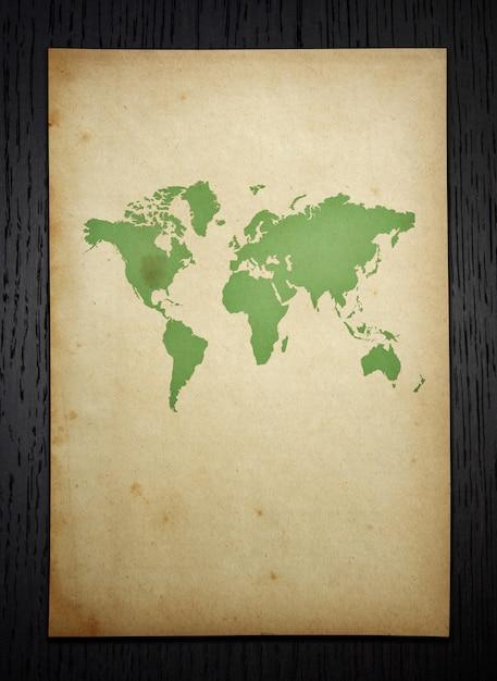 Mapa mundial do vintage no fundo de madeira escura com trajeto de grampeamento Foto gratuita
