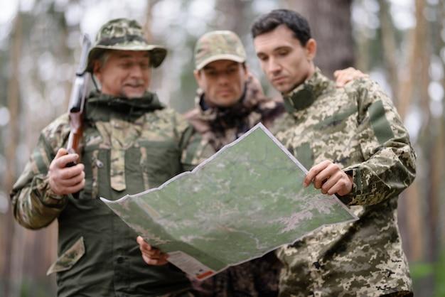 Mapa topográfico em mãos de caçadores na floresta. Foto Premium