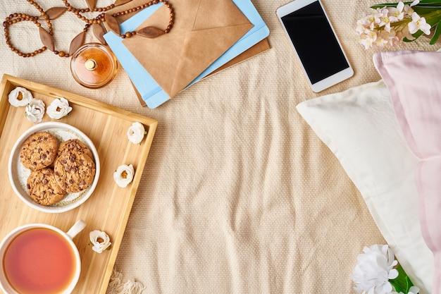 Maquete com acessórios femininos na cama chá, biscoitos, travesseiros, flores, carta, caderno Foto Premium