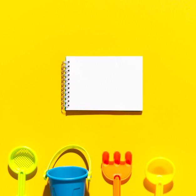 Maquete com bloco de anotações em branco para texto e brinquedos Foto gratuita