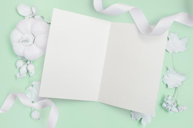 Maquete com fita branca, abóbora, bagas e folhas sobre um fundo verde Foto Premium