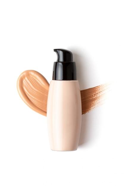 Maquete com maquiagem rosto fundação garrafa e gota borrada de corretivo sobre o fundo branco Foto Premium