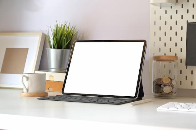 Maquete da tabuleta com teclado inteligente na tabela de espaço de trabalho mínima. Foto Premium