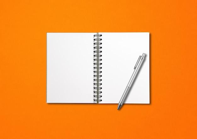 Maquete de caderno espiral aberto em branco e caneta isoladas em fundo laranja Foto Premium