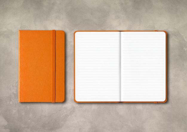 Maquete de cadernos forrados de laranja fechada e aberta isolada no fundo de concreto Foto Premium