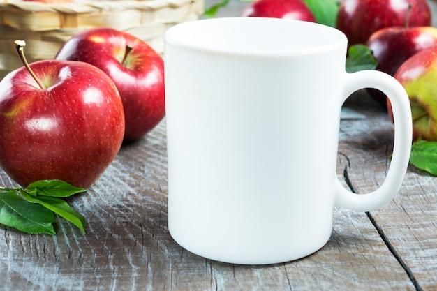 Maquete de caneca de café com maçãs Foto Premium