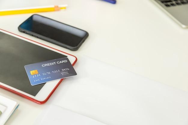 Maquete de cartão de crédito falso no computador tablet e smartphone com o laptop na mesa Foto Premium