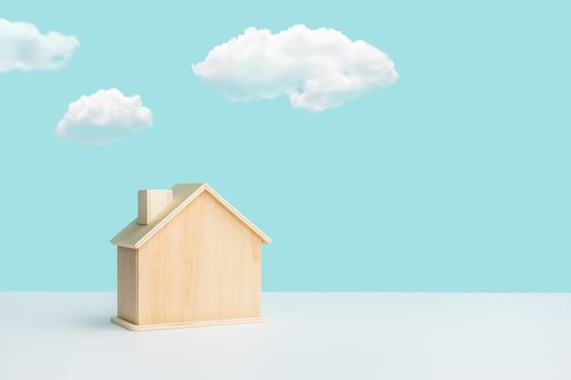 Maquete de casa feita em madeira com céu sobre fundo cor pastel Foto Premium