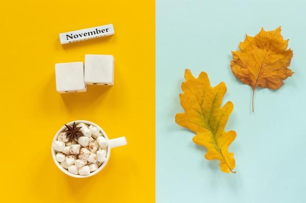 Maquete de cubos em branco e novembro para seus dados de calendário, xícara de cacau e folhas de outono amarelas Foto Premium