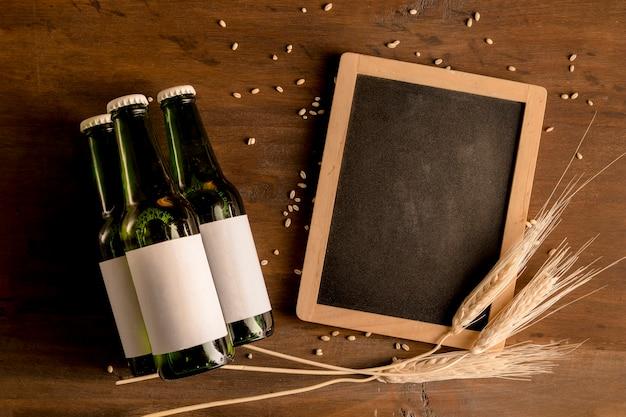 Maquete de garrafas verdes de cerveja com quadro negro na mesa de madeira Foto gratuita