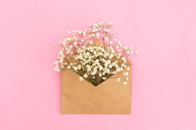 Maquete de gypsophila flores no envelope na vista superior de fundo azul no estilo leigo plana Foto Premium
