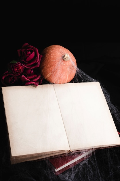 Maquete de livro com rosas e abóbora Foto gratuita