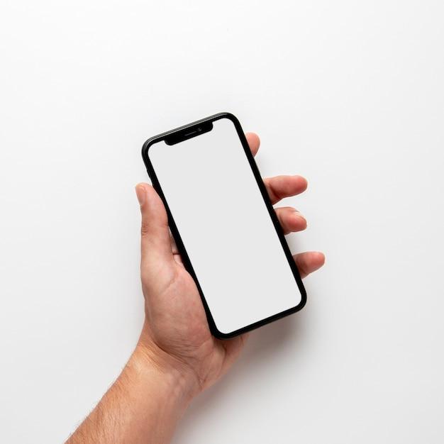 Maquete de mão segurando o telefone Foto Premium