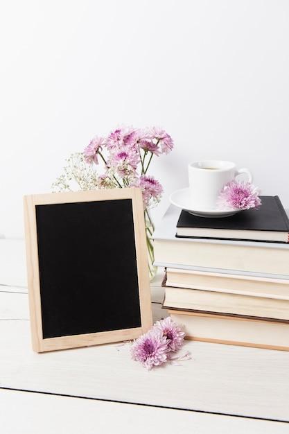Maquete de quadro ao lado de livros Foto gratuita
