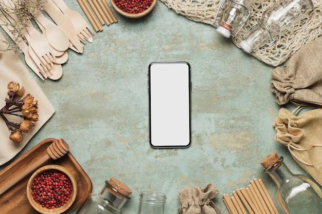 Maquete de telefone com objetos ecológicos Foto gratuita