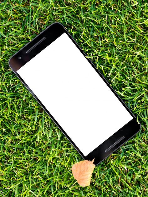 Maquete de telefone inteligente móvel com tela branca em fundo de grama verde e outono amarelo le Foto Premium
